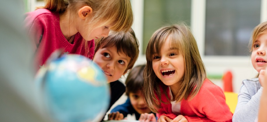 Photo of children looking at a globe.