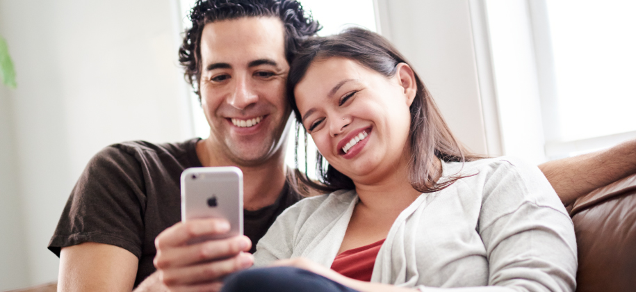 Photo of couple looking at mobile device.